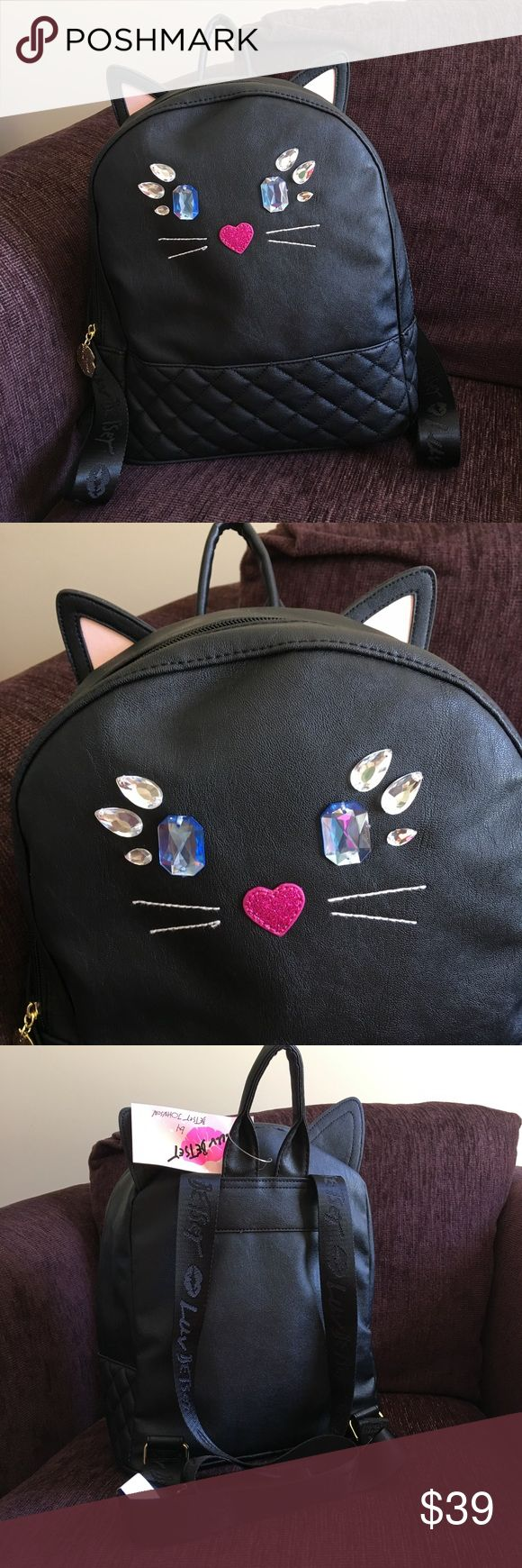 """Luv by Betsey Johnson Cat Bling Backpack NWT Adorable black cat kitty backpack with ears LBLUCY Luv by Betsey Johnson. Rhinestone Blue Eyes And Clear Eyelashes With A Pink Glitter Heart Nose on the front, Quilted Bottom, Gold toned Hardware, Zip Closure And Camouflaged """"Luv Betsey"""" On Adjustable Straps. The interior is Fully Lined Gray White Dots And Stars, with Slip Pockets And Zippered Pocket. 12""""H x 10""""W x 6""""D. Straps up to 26"""". It was kept in a smoke free home. Betsey Johnson Bags…"""