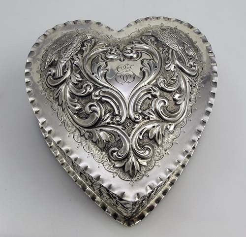 """4931 Dominick & Haff Sterling Heart Box    A large sterling silver hand chased heart box made by Dominick and Haff in 1890 and retailed by Bigelow Kennard and Company. Monogrammed in the cartouche between two hand chased birds on the lid. The sides are also hand chased with an ornate panel. The lid pulls off. Weight: 8.7 troy ounces. 5 1/2"""" by 5"""". Excellent condition.     Price: $975.00"""