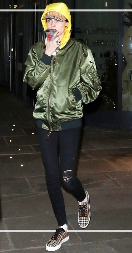 Cara Delevingne wears a Burberry cap, bomber jacket and trainers.
