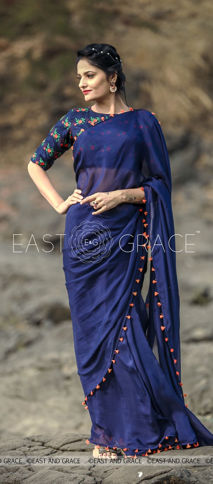 PRICE: INR 6,321.00; US$ 95.77 To buy click here: https://goo.gl/FdPrde Featuring the Blue Flame saree in deep navy blue, 100% flat, pure silk chiffon fabric with neon orange tassels decorated along the edges. The synthetic raw silk blouse has neat, fresh orange flowerbeds embroidered with green foliage that stand out against the stark navy blue backdrop for beautiful results, as though emulating the bright sparks from a blue flame. Reach us at care@eastandgrace.com. With Love, EAST & GRACE…