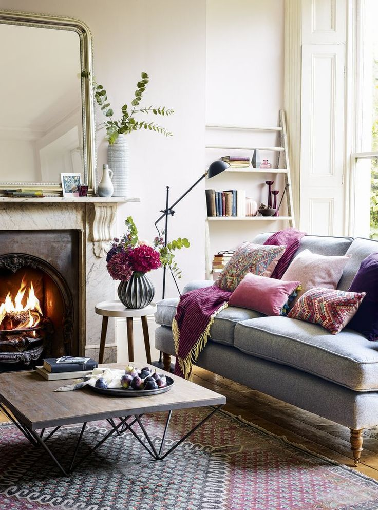 To create a cosy fireplace setting  layer up with soft furnishings, so introducing pastel shades with textured cushions and throws is good here. Accessories with plant pots for a calming and relaxing environment. (Photography by Dan Duchars). For more hygge ideas visit housebeautiful.co.uk