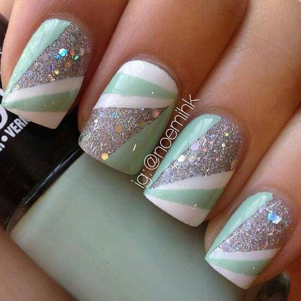 Abstract themed glitter nail art design in silver glitter with white and light green polish.