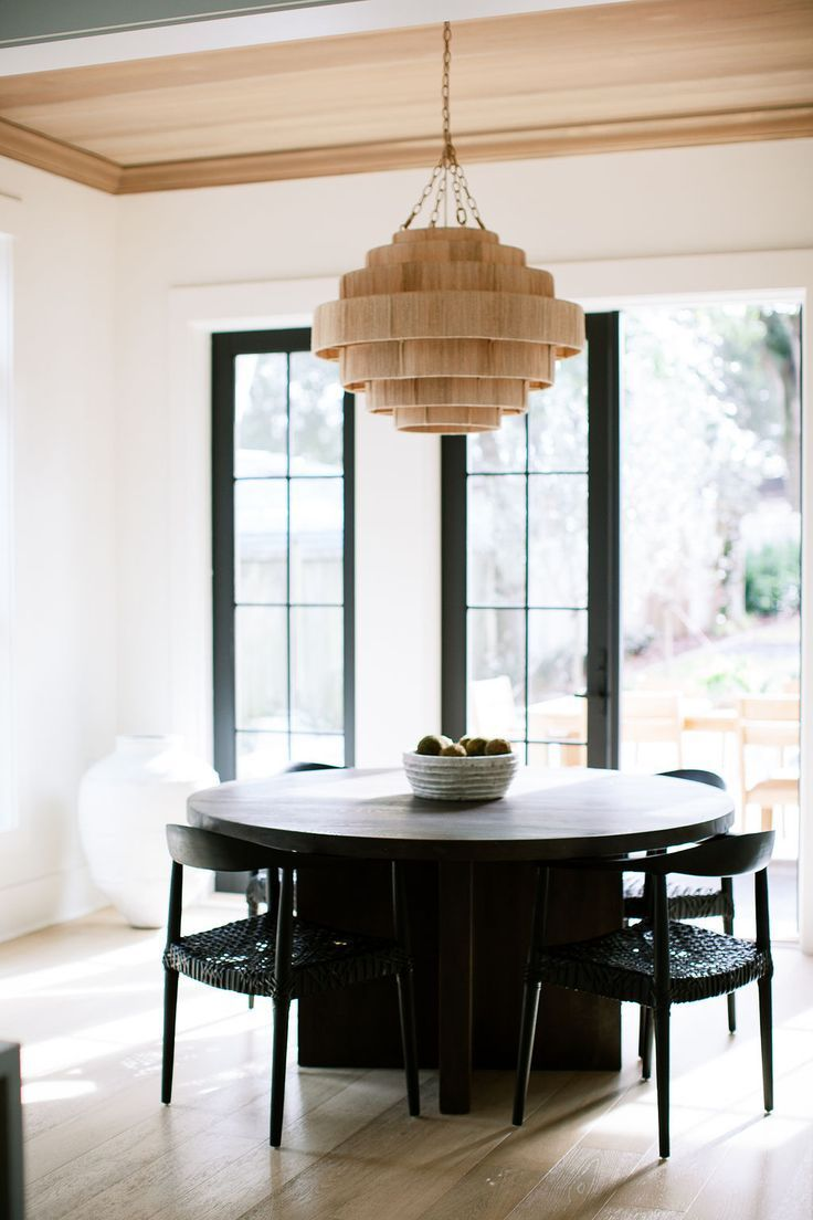 Black Modern Round Dining Table With Matching Black Seating And Contrasting Wicker Pendant Light Dining Decor Dining Room Design Dining Room Chandelier