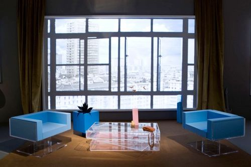 Prada's 'Ideal House,' decked by Architecture's OMA has a neutral area rug, clear plastic coffee table, and bright blue furniture.