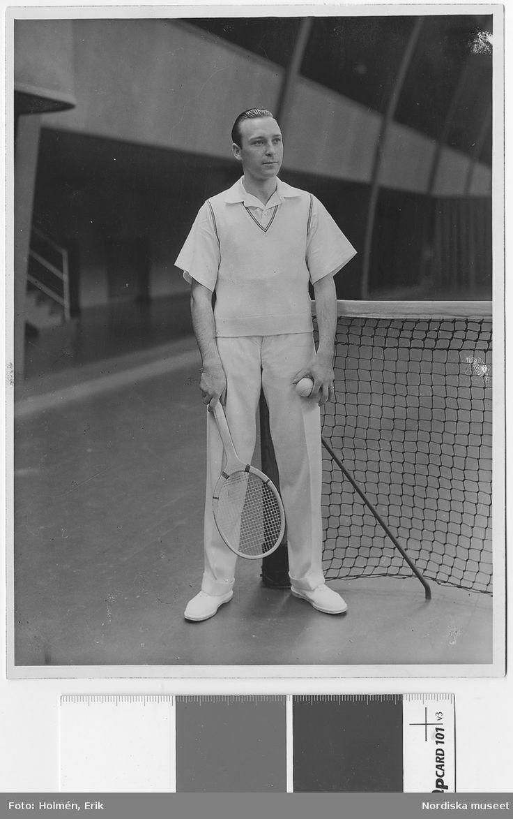 1930. Man i vit skjorta, vit slipover och vita byxor bredvid ett nät. I ena handen ett tennisracket, i den andra en boll. Nordiska Kompaniet. Fotograf: Erik Holmén