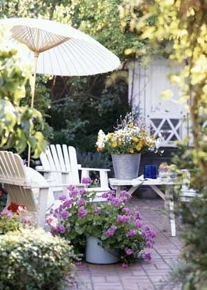 Adirondack chairs are a favorite addition to a country patio. Bright bunches of flowers complement this cozy seating area, and a white parasol offers shade and a touch of whimsy.