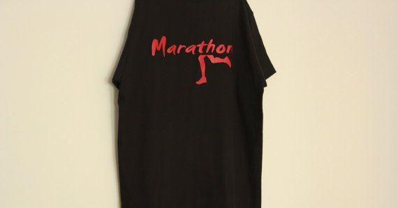 Camiseta de algodón en la que destaca el dibujo y la marca Marathon. Las piernas de un corredor traspasando infinitud de kilómetros.