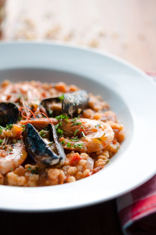 Quickly and easily prepared typical Sardinian pasta fregola sarda with rich seafood sauce.
