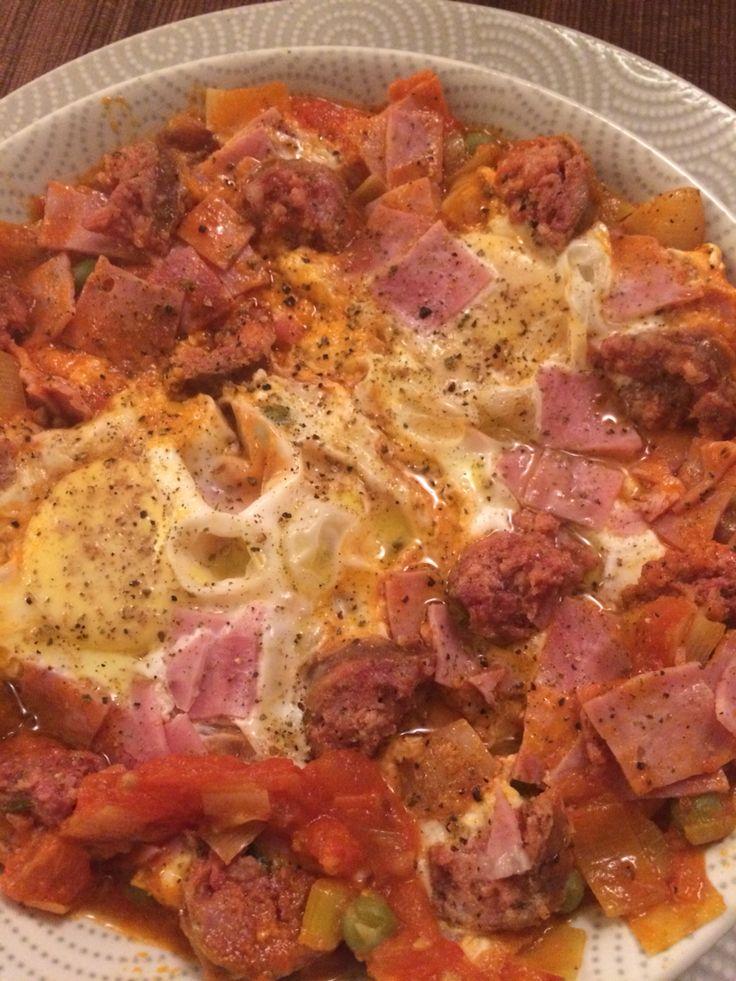Huevos a la flamenca: - huevos de gallina feliz - tomate natural - puerro - longaniza de Chillan - jamón - arvejas - aceite de oliva - 1/2 cucharadita de azúcar  - toque de pimienta molida