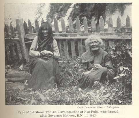 Black and White photograph of two older Maori Women sitting in the front of a fence.