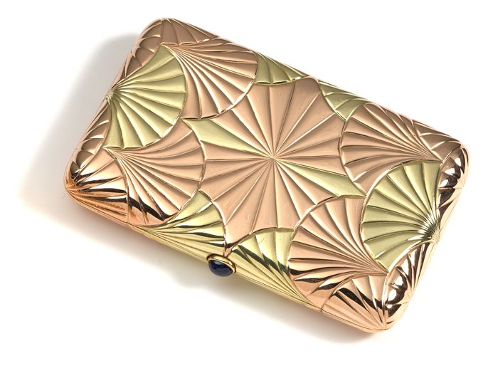 A coloured gold cigarette case by Carl Fabergé    decorated with fans of red and green gold invisibly soldered  together, the pattern repeated throughout the case, the   thumbpiece set with a cabochon sapphire.      Workmaster August Hollming,    St. Petersburg, 1899-1908.