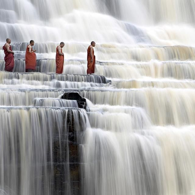 In a peaceful mood... Monks passing Pongua Falls, Vietnam. Located in a mountain range more than 50 kilometers from Dalat, Pongua water fall is as high as 40 meters. From that height water falls down to a big lake below producing great noise the echo of which can be heard far from the fall.