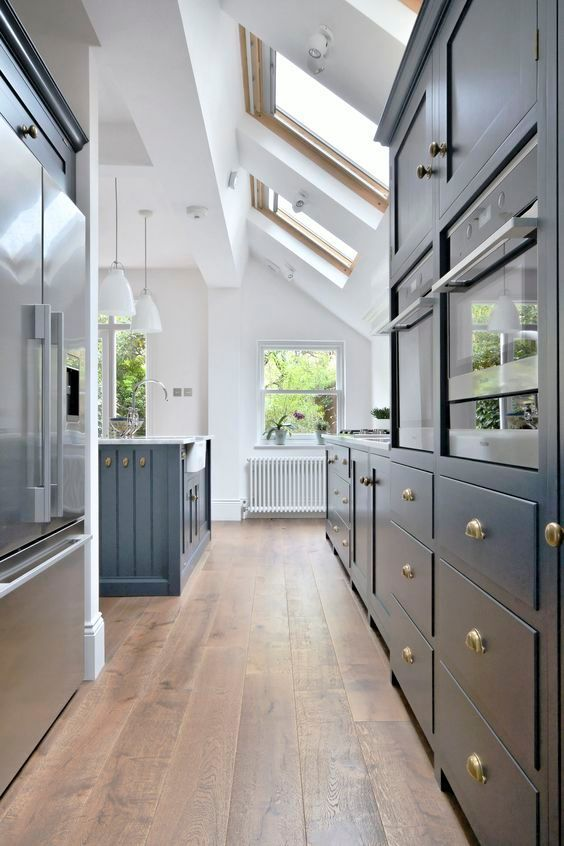 Spacious and bright kitchen in a tight space: Roof windows, white walls and dark blue wooden furniture.