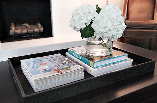 A Dark Wood Coffee Table With Faux Leather Tray Stacked With Magazines Books And A Glass Vase