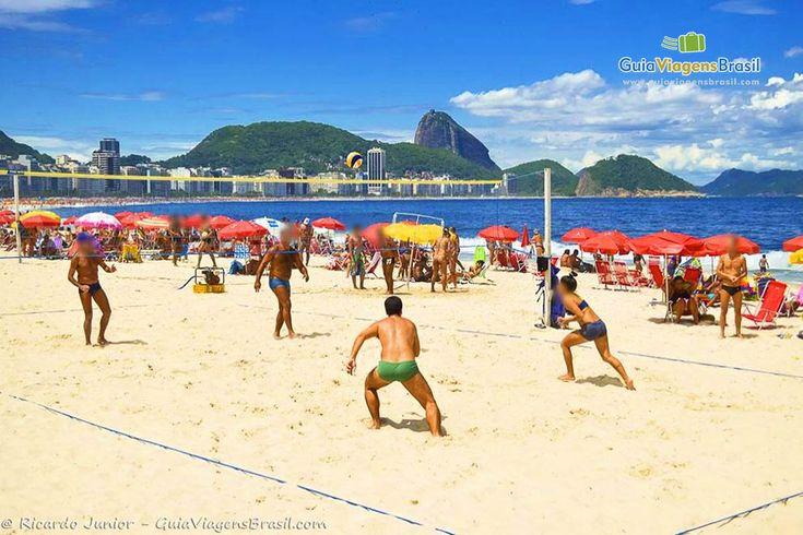 Imagem de meninos e meninas praticando vôlei na praia.