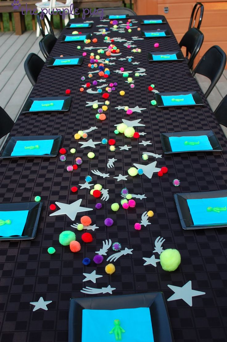 Table décor- black tablecloth, neon pompoms, glow in the dark stars