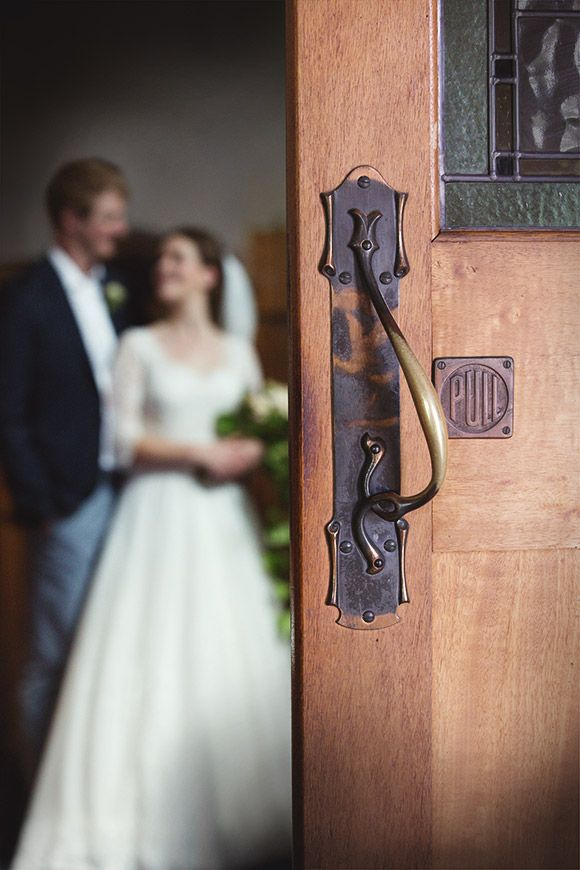 I love this shot of the bridal couple inside the church with the church door in focus :)