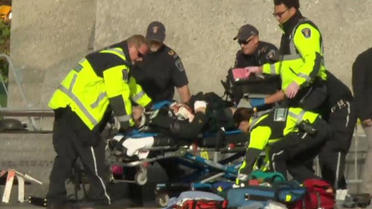 Emergency responders desperately work to save the life of the wounded soldier at the National War Memorial
