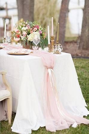 Delicate gathered blush table runner atop a sweetheart table with beautifully arranged white linens and gold accents.