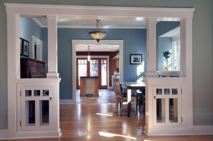 The warm, inviting kitchen opens up to a pretty blue dining room, creating an easy flow through the main areas of the home. Beautiful architectural details, like the structured columns and room dividers, add to the Craftsman feel of space.