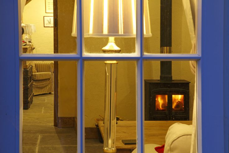 View of one of the log fires through the window at Glandwr Farmhouse - Our luxury holiday cottage.