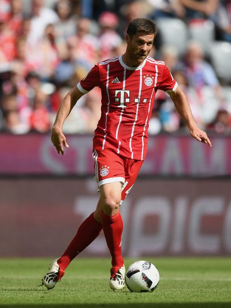 Xavi Alonso of FC Bayern Muenchen controls the ball during the Bundesliga match between Bayern Muenchen and SC Freiburg at Allianz Arena on May 20, 2017 in Munich, Germany.