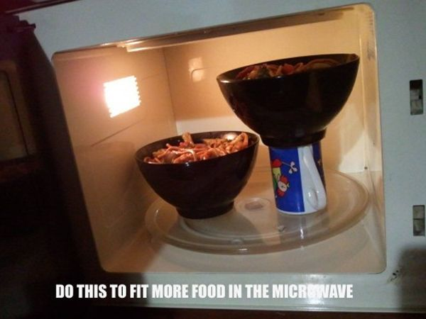 Stack bowls and plates on coffee mugs to increase microwave capacity