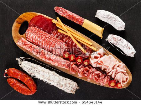 Assortment of different sliced meat snacks. Serving cold Italian appetizers On black natural stone from slate. On a wooden board from olive tree and whole sticks of sausages