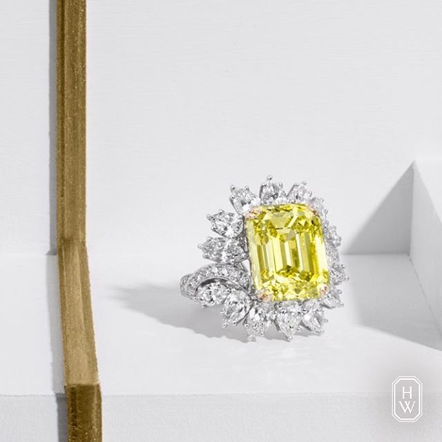 Harry Winston. A 12.61-carat Emerald-Cut Yellow Diamond Ring, artistically surrounded by 43 diamonds.