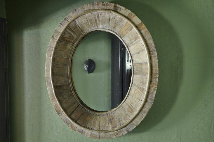 Laura Silverman's house,  Mirror Michael Mund, A small hallway glows with Farrow & Ball's Calke Green, a color based directly on a cleaned version of the breakfast room at Calke Abbey. The reclaimed teak mirror frames a bronze mask brought back from a trip to Java./Remodelista