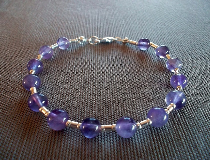 Handcrafted bracelet featuring 6mm round genuine amethyst beads and sterling silver beads and clasp. 8 inches in length.