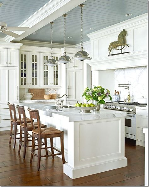 Stunning white kitchen. Love the blue ceiling and wood tone barstools.