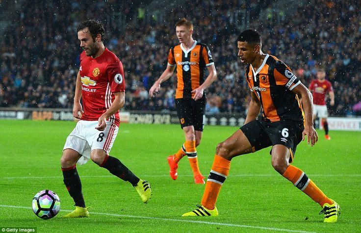 Juan Mata is ushered away from the Hull goal by captain and defender Curtis…