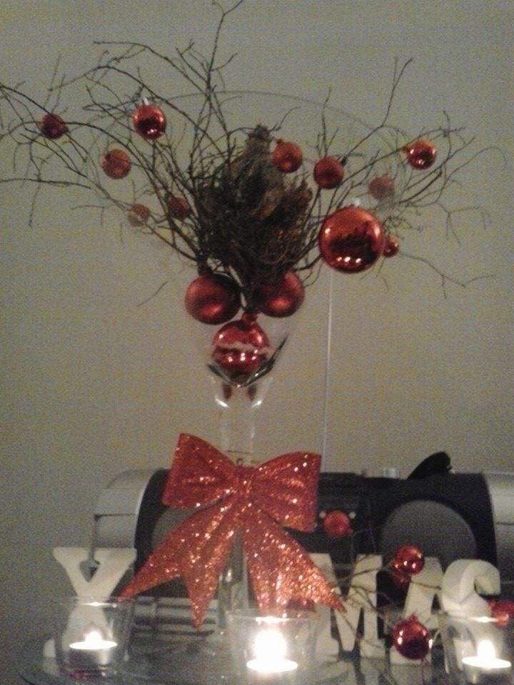 X mas met kerstballen aan takken, amarylis in een groot glas.