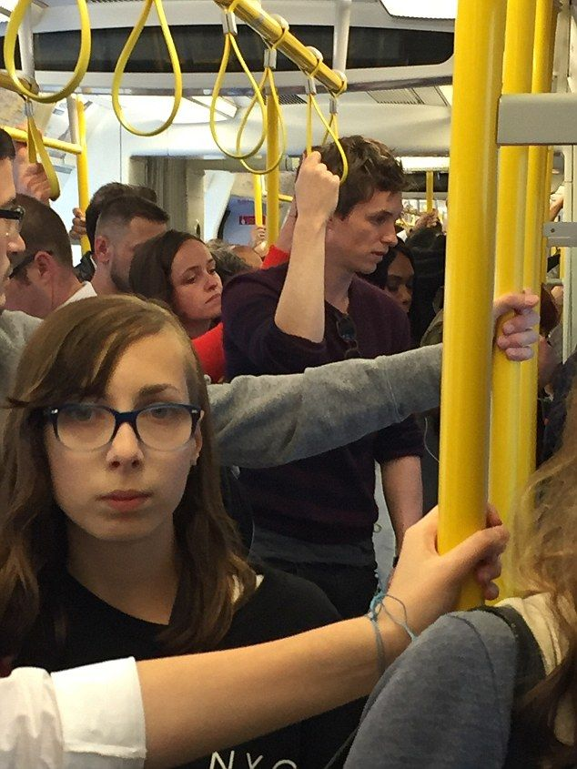 Blending in with the crowd:Eddie Redmayne was spotted on the Tube with his wife Hannah on Tuesday,riding a busy Circle line carriage towards Victoria at rush hour