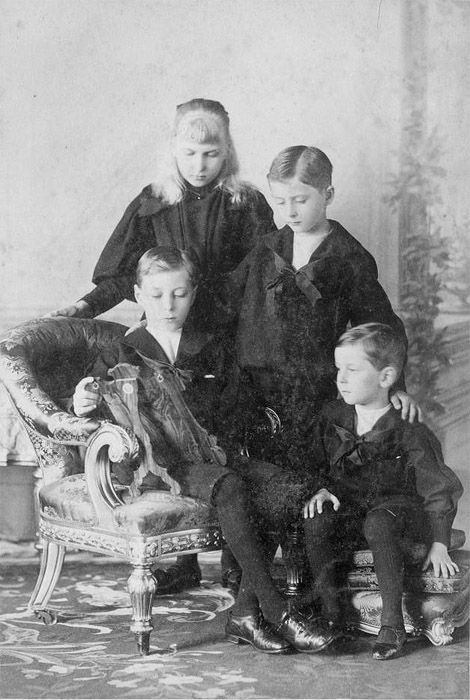 Four of Queen Victoria's grandchildren, the children of Princess Beatrice and Prince Henry of Battenberg. They are Prince Alexander (1886-1960), Princess Ena (1887-1969), Prince Leopold (1889-1922) and Prince Maurice (1891-1914). This is a mourning photograph, commemorating the death of their father. They are all looking at a photograph frame, it's most likely a picture of their father. He died of malaria whilst serving with the Britsh Army out in West Africa in 1896, aged 38.