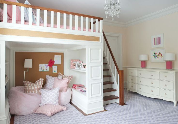 Fun girl's bedroom features a built-in staircase leading to a loft bed dressed in pink and blue bedding positioned over a play nook filled with a purple trellis rug topped ith pink velvet bean bags under built-in cork board flanked by built-in bookcases alongside a 9 drawer dresser is topped with pink block table lamps.
