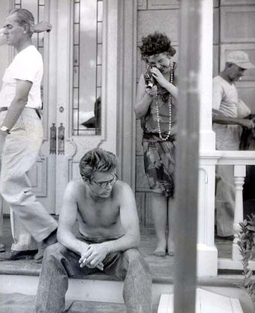 A movie extra films a pensive James Dean during a break on the set of Giant, 1955