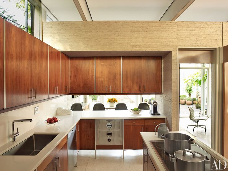 A midcentury-modern marvel nestled in an enclave of Victorians, architect Lee Ledbetter's home is quite different from the typical New Orleans estate. The landmark 1963 house—a collection of volumes wrapped with steel columns and arches—was purchased by Ledbetter and his partner in 2013, and the architect set about updating the space while retaining its modernist charms. The new kitchen opens up to a breakfast area and courtyard, giving it a communal feel. The original walnut cabinetry and…