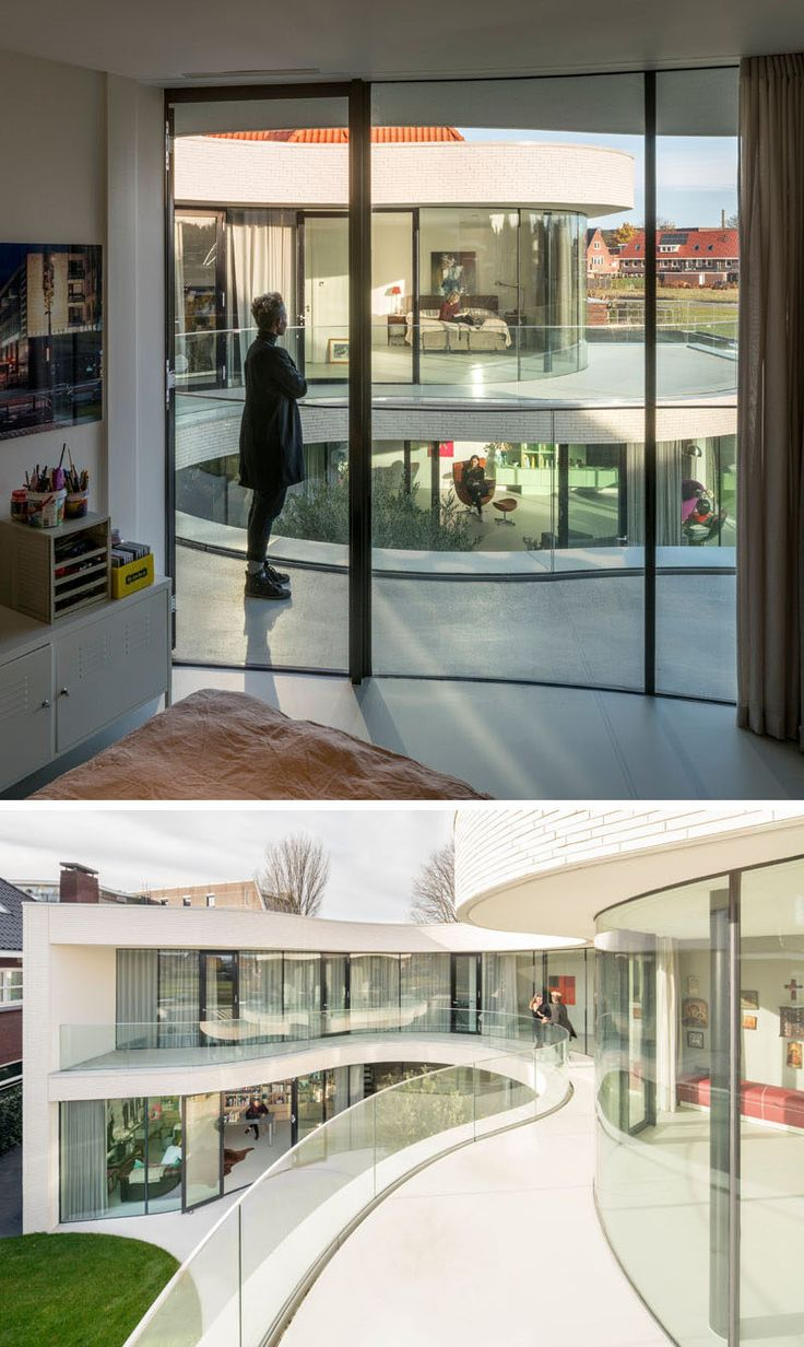 The floor-to-ceiling curved glass windows and doors on the upper floor of this modern house open up to the wraparound balcony.