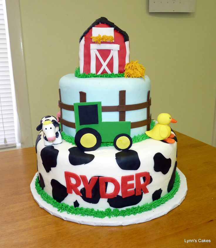 John Deere Tractor Farm Cake - Vanilla cake iced in buttercream.  Tractor, animals, cow print, fence are fondant.  Barn is rice krispie treats covered in fondant.