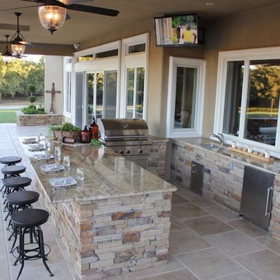 What an awesome outdoor kitchen and a great place to entertain guests! Gorgeous counter tops, tile, and stonework! #OutdoorKitchen #OutdoorSpaces