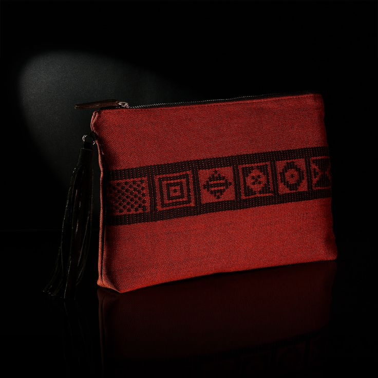 Τhe handmade woven envelope adorns patterns from Greek history and tradition. The background is in cinnamon color and the embroidery in black color.