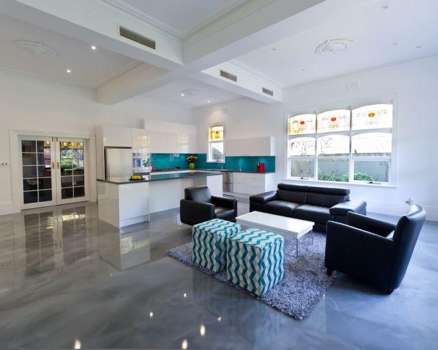 un revêtement de sol en résine gris clair et brillante dans le salon ouvert sur la cuisine