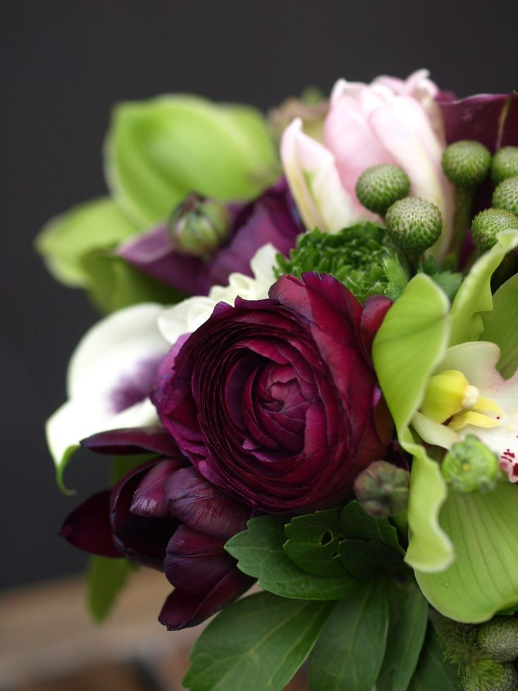 a bundle of soft pink tulips placed amongest things greens crowned with a ranuncula  dripping with purple color
