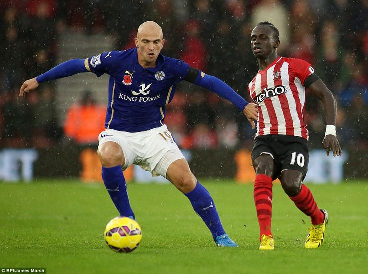 Leicester midfielder Esteban Cambiasso (left) shields the ball away from the challenge of ...