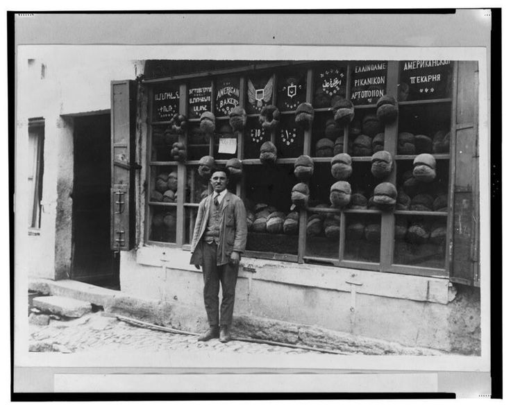 "Baker standing in front of the ""American Bakery"" which displays signs in Armenian, Ladino (in Hebrew characters), English, Ottoman Turkish, Greek and Russian with samples of bread attached to the mullions, 1922, Istanbul, Turkey."