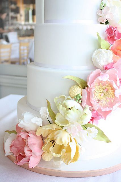You can turn plain white cakes into a beautiful wedding cake by using satin ribbon and coordinating fresh flowers or in this case have the bakery make these life like sugar flowers.