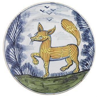 A LAMBETH DELFT POLYCHROME 'FOX' DISH  CIRCA 1740  Naively painted with an orange-striped yellow fox outlined in blue with raised tail and right foreleg and whiskers, flanked by blue sponged trees, standing on a green mound with a flock of four birds in the cloudy sky above  11½ in. (29.3 cm.) diam.