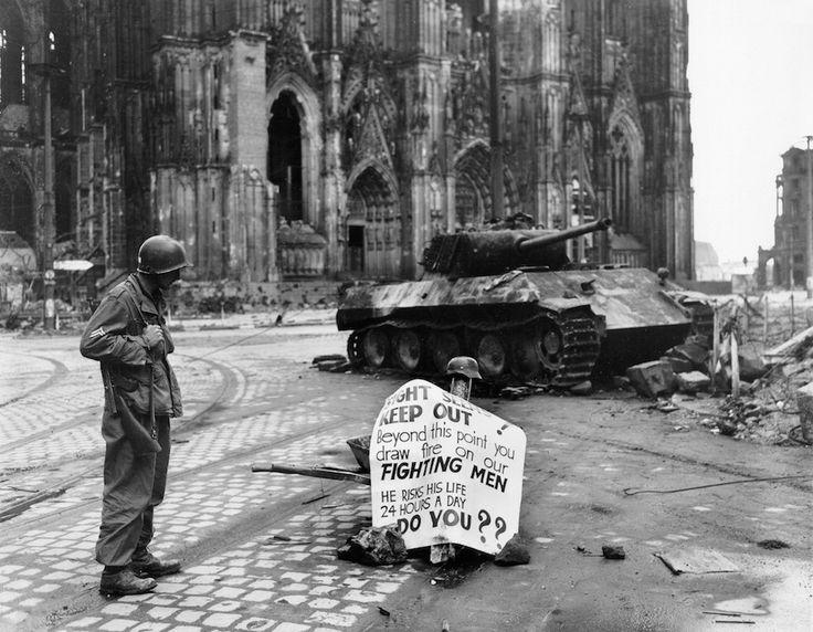 Le caporal Luther E. Boger d'US 82e Division aéroportée, lire un panneau de signalisation, Cologne, Allemagne, 4 avril 1945 ; Notez la mitraillette Thompson et panthère réservoir épave  Corporal Luther E. Boger of US 82nd Airborne Division reading a warning sign, Cologne, Germany, April 4, 1945; note Thompson submachine gun and Panther tank wreck